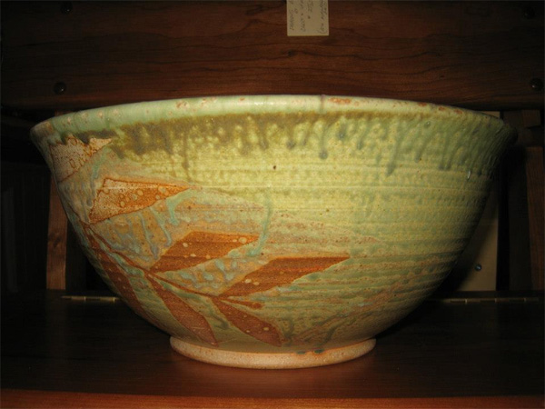 Bowl with brown leaf pattern on light green background.