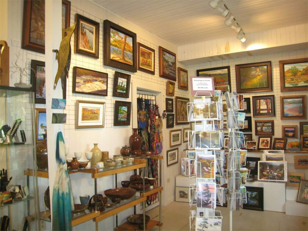 Paintings hanging on the wall and other items on shelves.